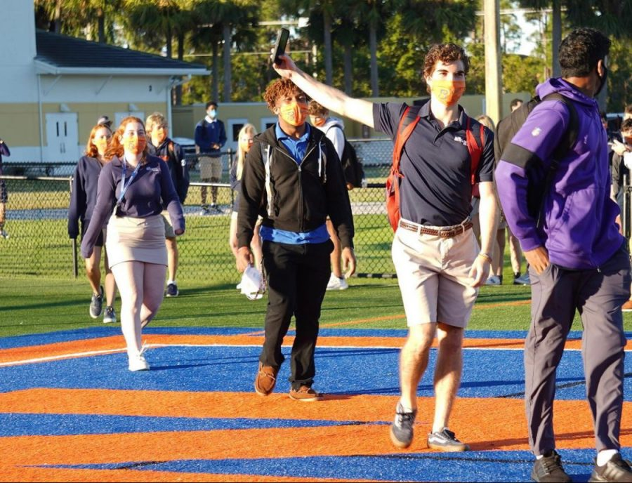 Seniors Cole Jernsted, Khani Johns, and Alex Kahn walk across the football field as they are clapped in by their peers.