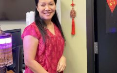 Chinese teacher Ms. Cohen poses in her traditional Chinese New Year outfit with one of the decorations in her classroom.
