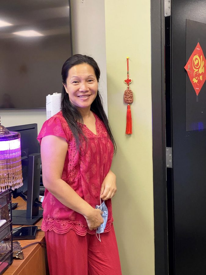 Chinese+teacher+Ms.+Cohen+poses+in+her+traditional+Chinese+New+Year+outfit+with+one+of+the+decorations+in+her+classroom.+
