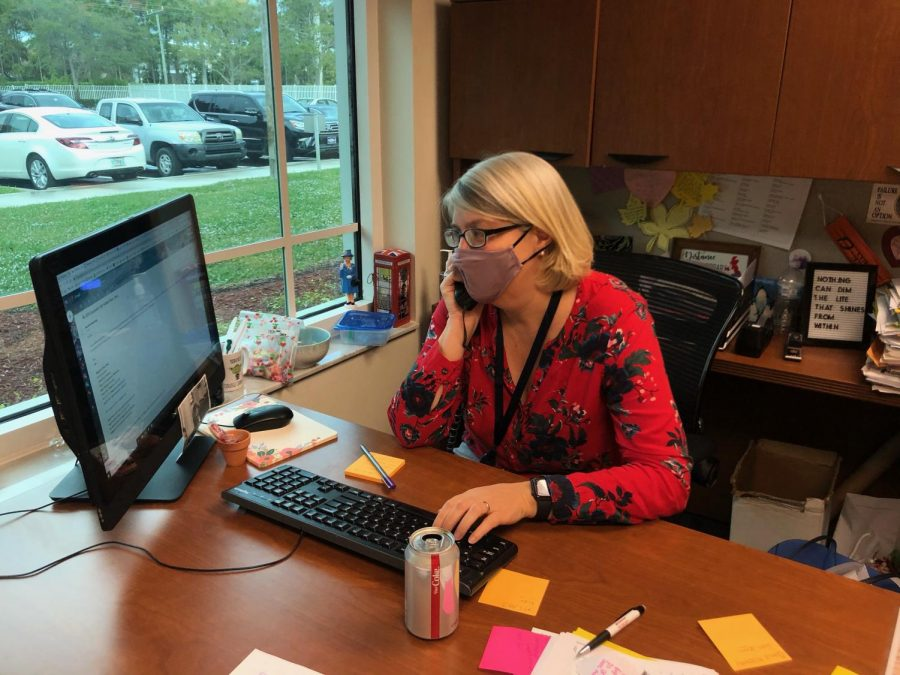 Director of College Counseling Ms. Anna Wright makes a phone call to a college. Despite applications being sent in first semester, the college counselors stay busy in the second semester helping juniors.