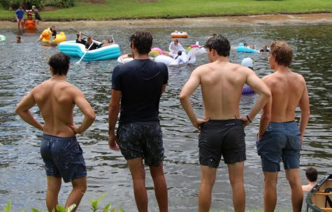 (L to R) Seniors Lukas Burnett, Nick Lutz, Andrew Pagano, and Lenny Lindahl watch their classmates enjoy themselves in the School lake on Apr. 30. Despite an unorthodox year due to COVID-19, the annual lake jump proceeded as normal.