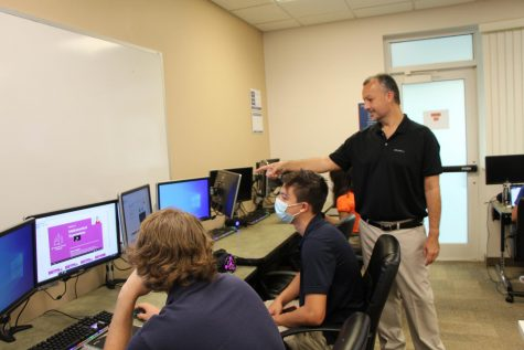 Computer teacher Mr. Brian Bray acts like a human mouse, pointing to to the screen as he instructs students in AP Computer Science.